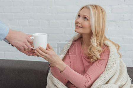 cropped careful grown son brought cup of tea to mother in blanket on sofa at home