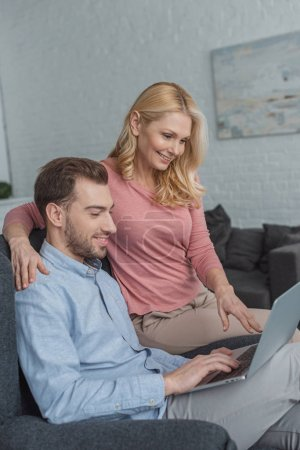 side view of mother and grown son using laptop together at home
