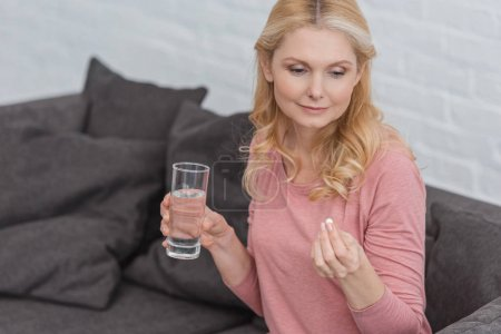 portrait of mature woman with glass of water and medicine in hands
