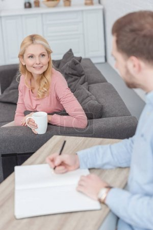 selective focus of smiling mother with cup of coffee looking at son at table with notebook at home