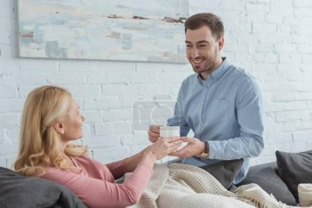side view of smiling careful son brought cup of tea to mother on sofa at home