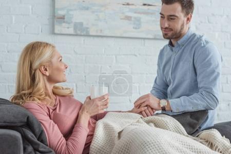 mère avec tasse de thé, couché sur le canapé avec un fils adulte près de chez vous