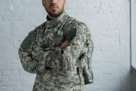 cropped shot of soldier in military uniform with arms crossed standing against white brick wall