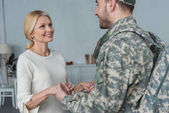 smiling mother and grown son in military uniform holding hands together at home