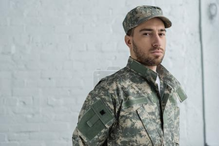 portrait of soldier in military uniform looking at camera against white brick wall