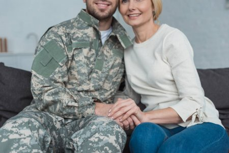 partial view of smiling mother and grown son in military uniform holding hands on sofa at home