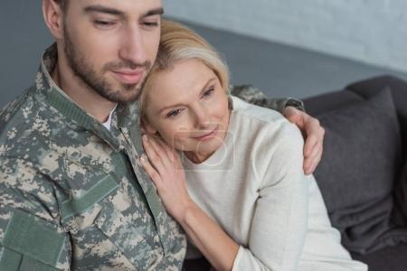 portrait of man in military uniform hugging smiling mother at home