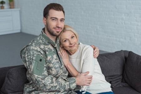 portrait of man in military uniform hugging smiling mother on sofa at home