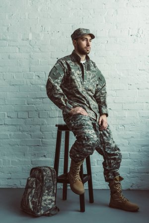 pensive soldier in military uniform sitting on chair against white brick wall
