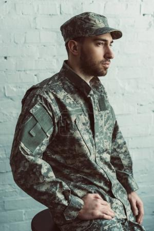 portrait of pensive soldier in military uniform sitting on chair against white brick wall