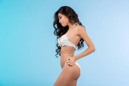 Photo for Brunette slim girl posing in white swimsuit, isolated on blue - Royalty Free Image