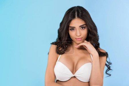 beautiful brunette slim girl in white bikini, isolated on blue