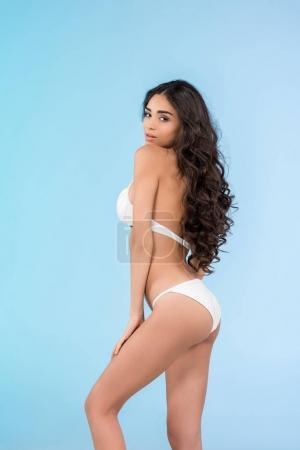 beautiful slim girl in trendy white bikini, isolated on blue