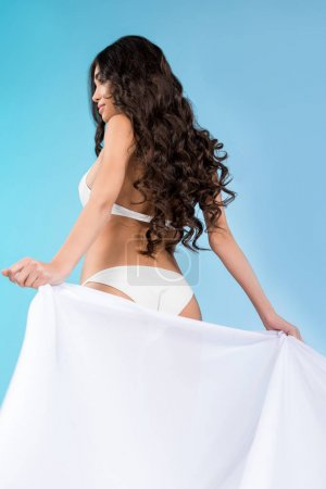 attractive brunette young woman in bikini posing with white veil, isolated on blue