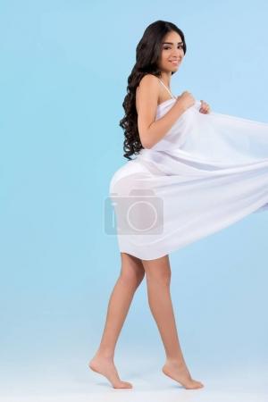 beautiful girl in white bikini posing with veil, isolated on blue