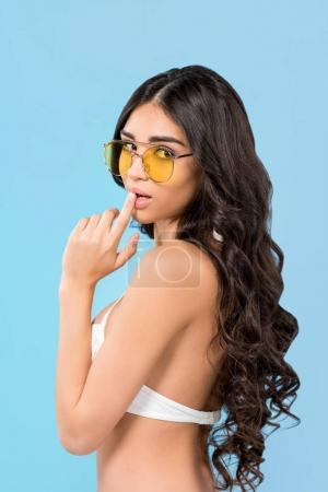 beautiful brunette girl posing in swimsuit and yellow sunglasses, isolated on blue