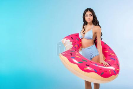 pretty girl posing with inflatable doughnut ring, isolated on blue