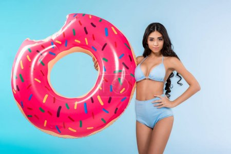 attractive girl posing with inflatable donut ring, isolated on blue