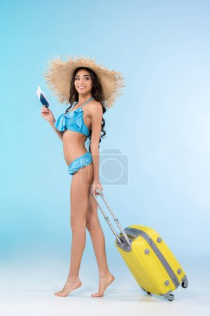 young woman in bikini and straw hat posing with travel bag and passport, isolated on blue