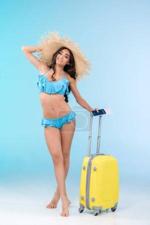 Photo pour Belle fille mince en bikini et chapeau de paille posant avec bagage et passeport, isolé sur bleu - image libre de droit