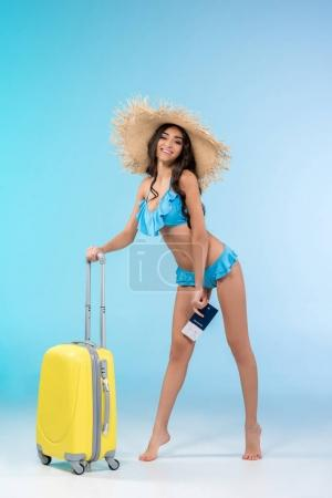 cheerful girl in bikini posing with luggage and passport, isolated on blue