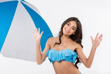 Photo for Beautiful smiling girl in bikini posing at beach umbrella, isolated on white - Royalty Free Image