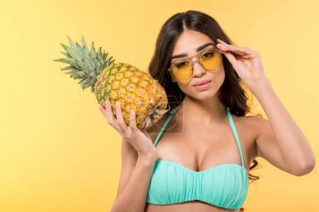 Photo for Attractive girl in sunglasses posing with fresh pineapple, isolated on yellow - Royalty Free Image