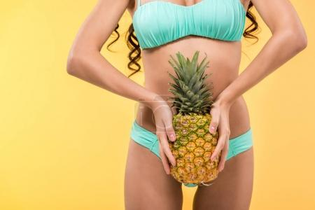 Photo for Cropped view of tanned girl holding pineapple fruit, isolated on yellow - Royalty Free Image