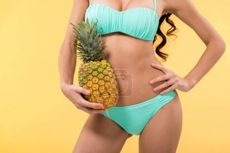 cropped view of slim girl holding fresh pineapple, isolated on yellow