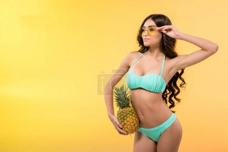 beautiful slim girl holding fresh pineapple, isolated on yellow