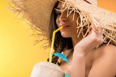 Photo pour Jolie fille en chapeau de paille tenant cocktail de noix de coco, isolé sur jaune - image libre de droit