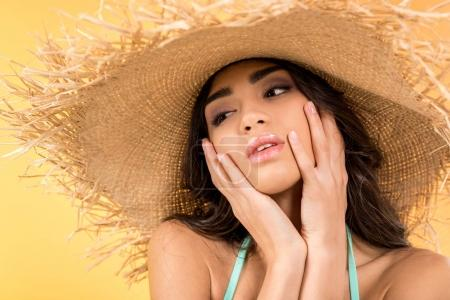 beautiful brunette girl in straw hat, isolated on yellow