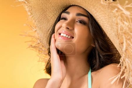 cheerful attractive girl in straw hat, isolated on yellow