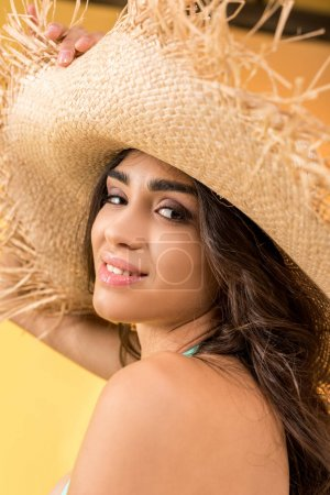 portrait of beautiful smiling girl posing in straw hat, isolated on yellow