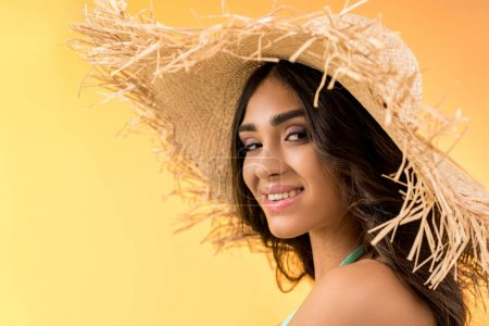 portrait of attractive girl posing in straw hat, isolated on yellow