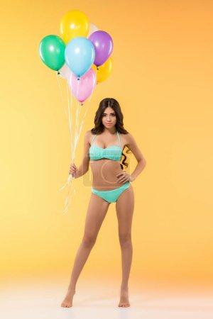 beautiful slim girl posing in bikini with colorful balloons, isolated on yellow