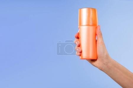 cropped view of person holding bottle of sunscreen, isolated on blue