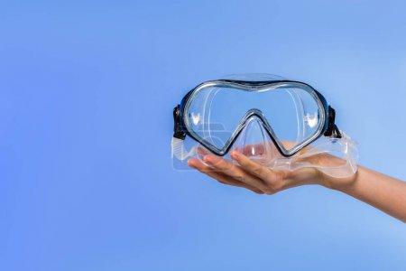 Photo pour Vue recadrée de la main féminine avec lunettes de natation, isolée sur bleu - image libre de droit