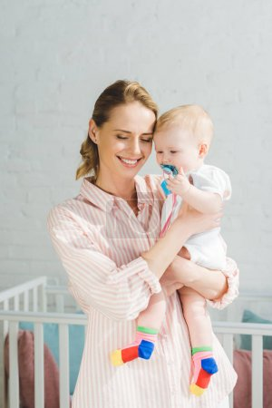 Smiling mother holding infant daughter with baby dummy