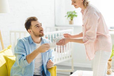 Photo pour Jeune femme verser le thé à petit ami avec coupe dans la main - image libre de droit