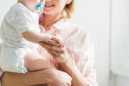 Cropped image of mother holding infant daughter with baby dummy