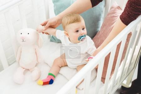 Cropped image of mother holding infant daughter sitting in crib