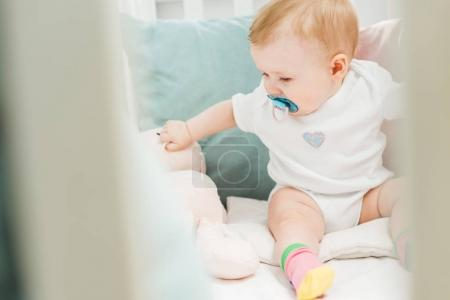 Infant with baby dummy and teddy hare sitting in crib