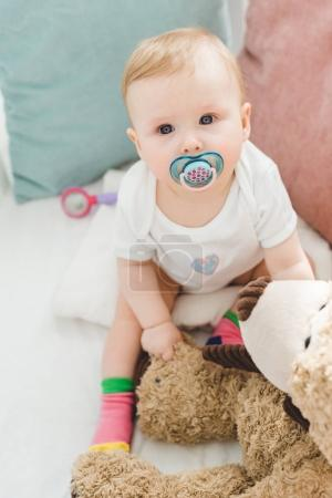 High angle view of infant with baby dummy and teddy bear sitting in crib