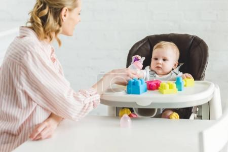 Mother feeding infant daughter sitting in baby chair with plastic blocks