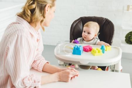 Mother watching at infant daughter sitting in baby chair with plastic blocks