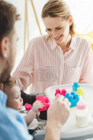 Parents with infant daughter sitting in baby chair with plastic blocks and feeding bottle