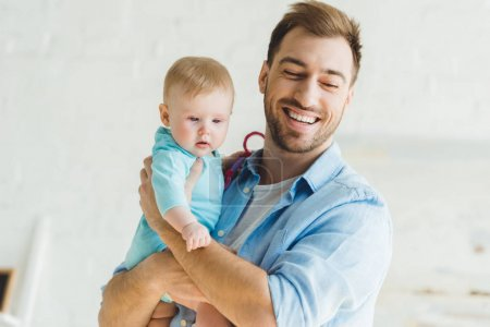 Happy young father holding infant daughter in hands