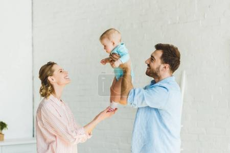 Father raising infant daughter while mother touching her legs