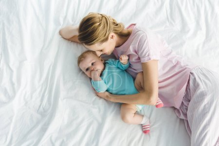 High angle view of smiling mother with infant daughter in bed
